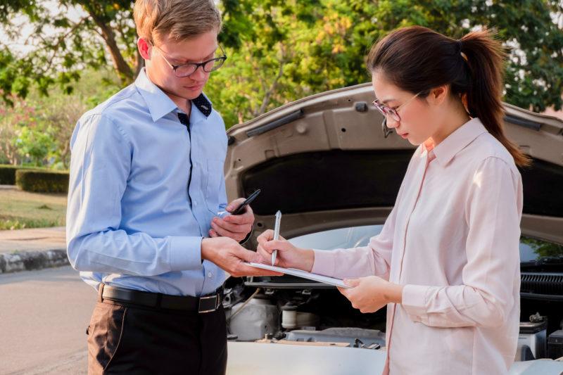 Agente de seguros escribiendo documento en el portapapeles examinando coche tras accidente, concepto de seguro