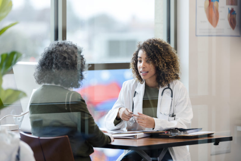 Sitting in office, doctor has serious conversation with patient