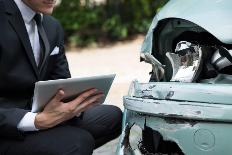 insurance adjuster evaluating car accident damage