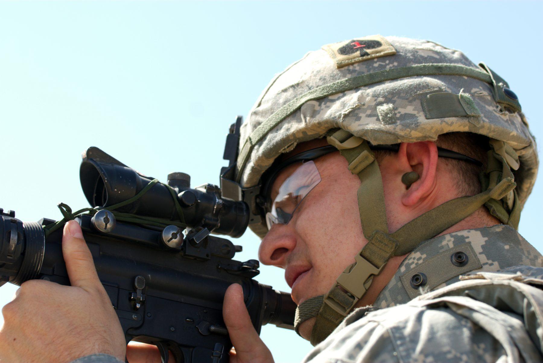 A man in combat wearing earplugs.