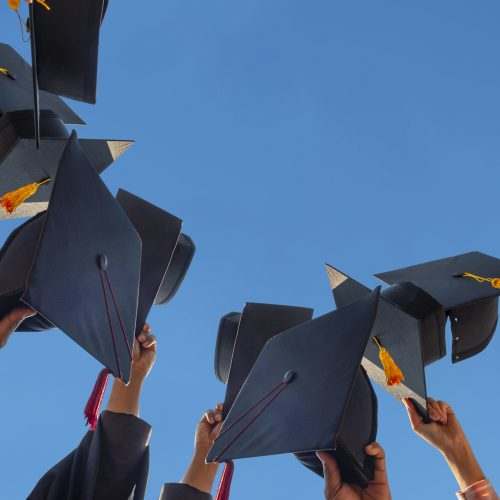 A group of graduates holding their caps in the air.